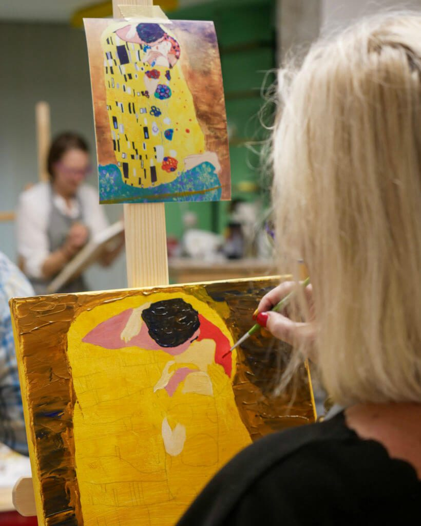 woman painting her interpretation of an artwork with instructor