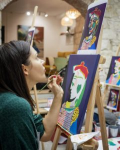 woman focuses on finishing her acrylic painting
